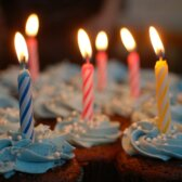 Chocolate cupcakes with white frosting and lit birthday candles