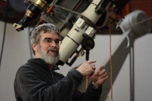Brother Guy gestures with his hands while talking, standing in front of a telescope