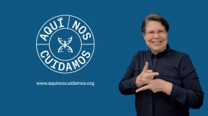 """An ASL interpreter smiles and signs against a blue background with the logo for """"Aqui nos Cuidamos"""""""