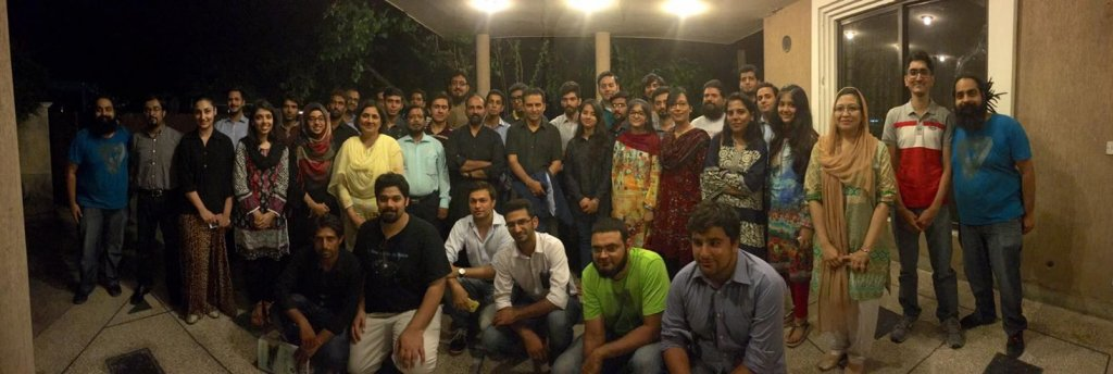 Salman Hameed poses with a group of about 40 people for a photograph at night