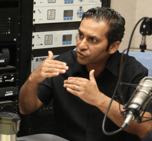 Salman Hameed sits in the radio studio next to a microphone and gestures with his hands
