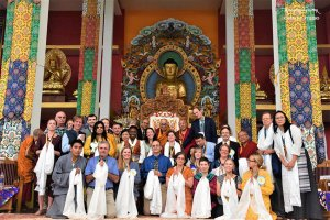 A group of around 30 people pose for a photograph in front of a large gold statue of Buddha