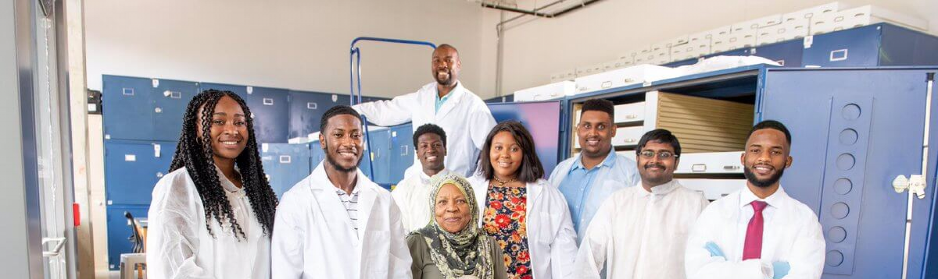 Fatimah Jackson sits on a stool, surrounded by eight members of her lab.
