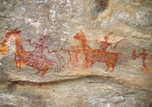 Red paint on a rock wall depicting people riding four-legged animals with long necks.