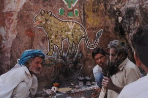 Four people in front of a wall painted with a leopard's image. One person holds peacock feathers.