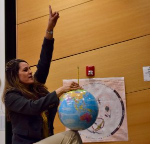 Annette Lee points her left index finger up to the ceiling while holding a globe on her right knee with her right hand