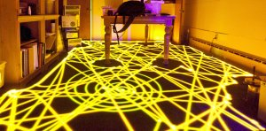 Glowing yellow trails are left on the floor of a room