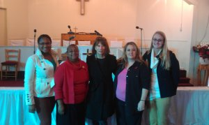 Pamela Payne-Foster with four members of Project FAITHH in front of a stage with a cross on the wall