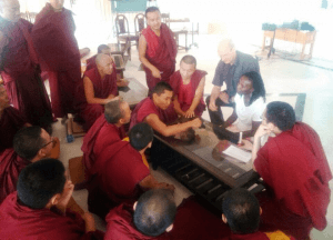 Gillian Hue sits at a low table with five monastic students, with more standing around the table, while one student at the table gestures with their arm