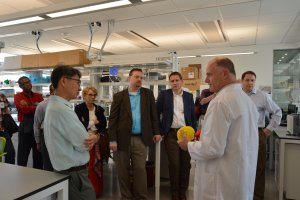 A scientist wearing a lab coat is talking to a group of people in a science laboratory.