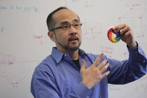 Francis Su stands in front of a white board with various mathematical figures on it, holding up a rainbow model of a torus